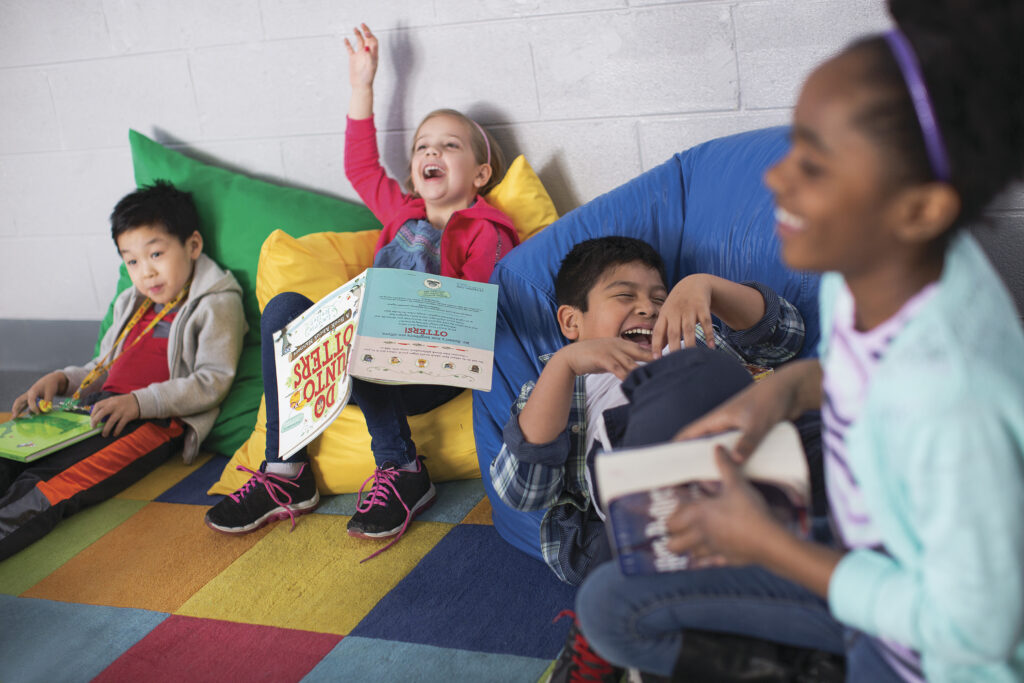 Four children laughing while sitting on beanbags